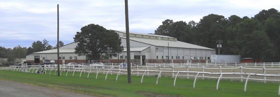 Indoor riding arena fronted by outdoor practice ring